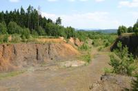 Pohled do v současnosti nečinného lomu Slap. V nadloží bazanitové lávy je zřetelná žlutavá poloha pliocénních fluviálních sedimentů., Vladislav Rapprich, 2010